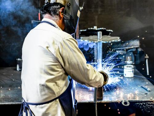 Manufacturing worker welds